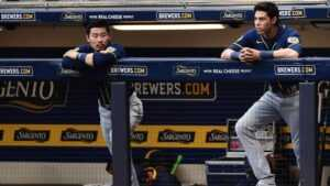 Brewers' outfielder Christian Yelich and second baseman Keston Hiura look on from the dugout during a 2020 regular season game.