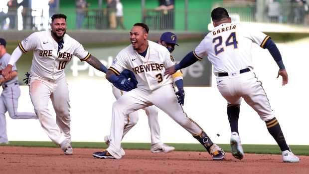 Orlando Arcia of the Milwaukee Brewers celebrates with teammates after driving in the game winning run during the tenth inning against the Minnesota Twins on Opening Day at American Family Field on April 01, 2021 in Milwaukee, Wisconsin. (Photo by Stacy Revere/Getty Images)